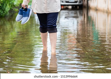 Woman walking on flooding road with holding shoes after the heavy rains,cause of itchy skin include,be careful of leptospirosis,it can be infected by contact with water,athlete's foot or tinea pedis