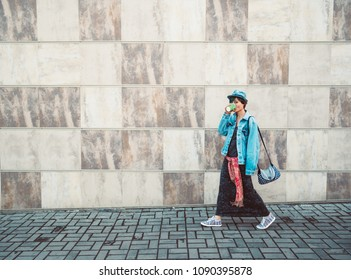 woman walking on gray wall background sidewalks outdoor corridor holding hot espresso coffee cup.