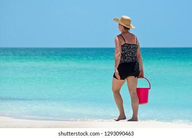 Woman Walking on Gulf Coast Beach in Florida carrying a Red Beach Bucket
