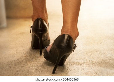 Woman walking on the high heeled shoe, some problem,broken right side high heeled shoe,her get injured her foot.