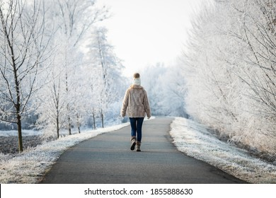 Frau geht im Winter im Park spazieren. Entspannen in der Schneewelt. Frauen, die warme Kleidung tragen, einen Strickhut mit Pom-Pom und Pelzmantel