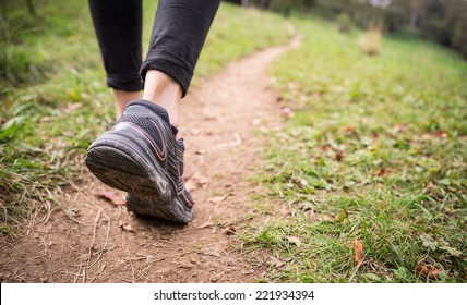 Woman walking on the path - Sportive girl running in a forest along a track