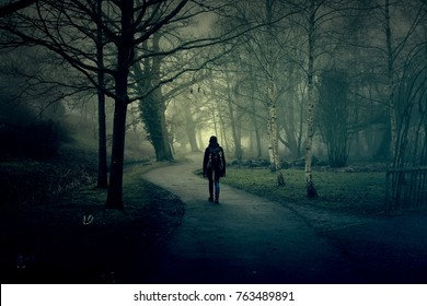 Woman walking on a path in a strange dark forest with fog