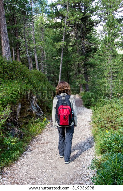 woman walking on a path in the woods with a backpack
