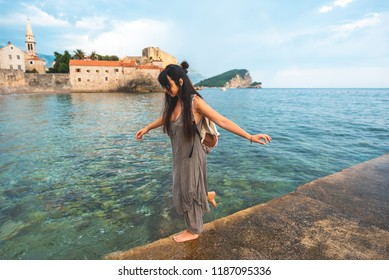 woman walking on pier side with Stari Grad (Old Town) on background in Budva, Montenegro