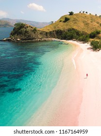 Woman walking on the Pink Beach in Indonesia.