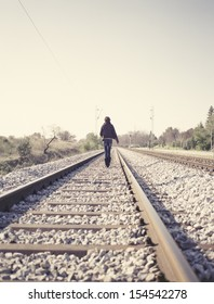 Woman walking on railway tracks