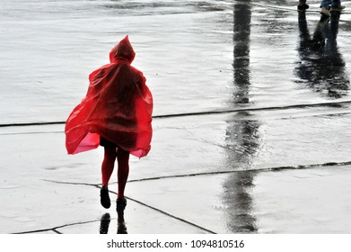 Woman walking on a rainy day wearing red raincoat.