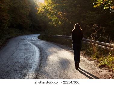 Woman walking on road in autumn afternoon. Beautiful autumn scene.