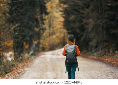 woman walking on the road with backpack Tourist