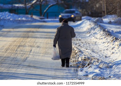 A woman is walking on the road in the snow in winter