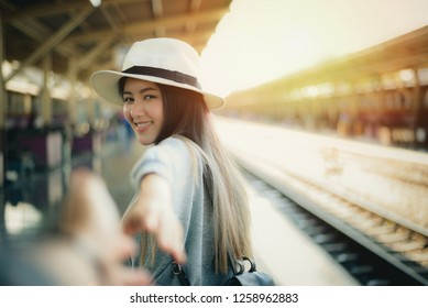 Woman walking on romantic honeymoon travel holidays holding hand of boyfriend following her,Lovely girlfriend inviting her boyfriend for traveling with her in train station,copy space.