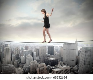 Woman walking on a rope over a cityscape