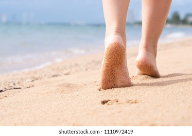 Woman walking on sand beach with barefoot leaving footprints in the sand. Summer beach concept