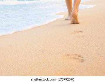 Woman walking on sand beach leaving footprint in the sand. Beach travel.