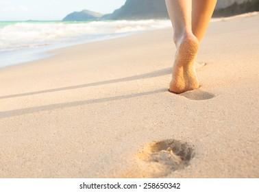 Woman walking on sand beach leaving footprints in the sand.