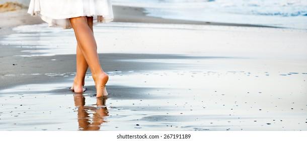 Frauen, die am Sandstrand spazieren und den Fußabdruck im Sand belassen