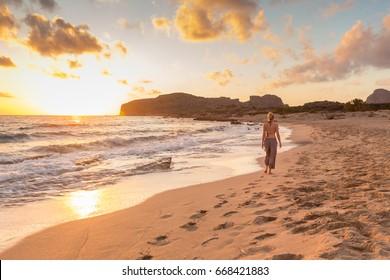 Woman walking on sandy beach at golden hour. Seashore sunset walk, Falasarna, Crete, Greece.