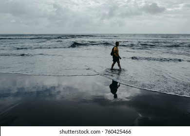 Woman is walking on sea beach. Sky reflected on wet sand. Film color toned