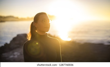 Woman walking on the seaside at sunset