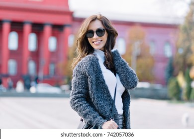 The woman is walking on the street with great smile. She has dark short hair and wonderful big blue eyes. She dressed in grey pullover and white shirt. Background urban city buildings