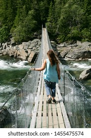 Woman walking on a suspension bridge