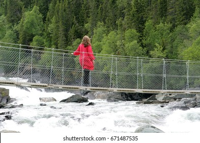 Woman walking on a suspension bridge over a stream