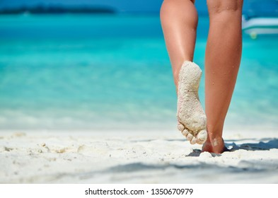Woman walking on tropical white sand beach. Summer vacation at Maldives.