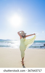 Woman walking on the trpical  beach in yellow dress
