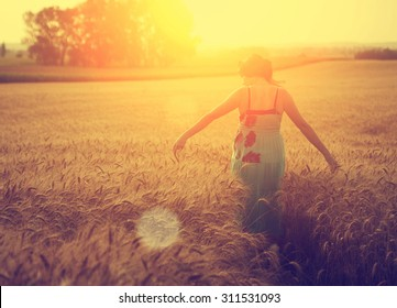 Woman walking on wheat field in sunset