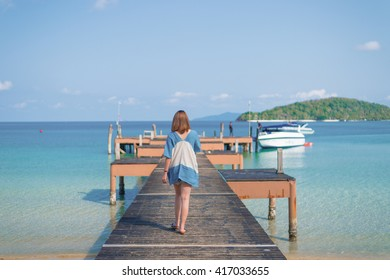 Woman walking on the wooden bridge with a clear blue sky and sea