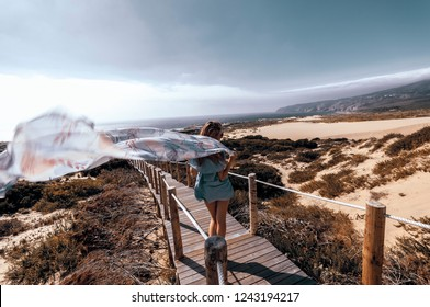 Woman walking on a wooden path on sand dunes in Portugal