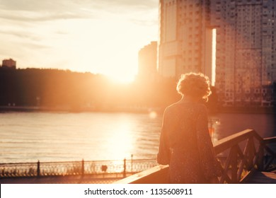 Woman walking on a wooden stairs near river bank in an urban landscape park at the sunset, looking to the side
