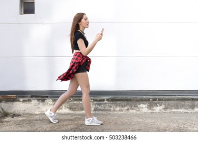 woman walking outdoor play internet her on mobile phone with wall white background