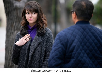 Woman walking outdoors in the city and looking snobby while running into an ex boyfriend or looking annoyed by an insulting stranger.  It also depicts social anxiety.