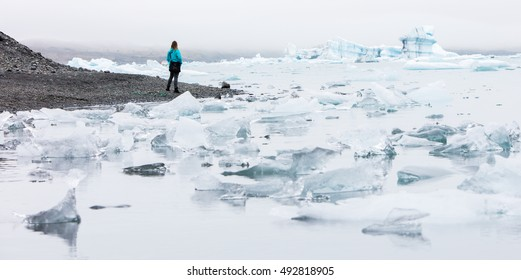 Woman walking over the beach at Jokulsarlon glacier lagoon in southern Iceland