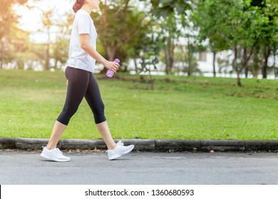 Femme marchant dans le parc avec de l'eau bouteille en été