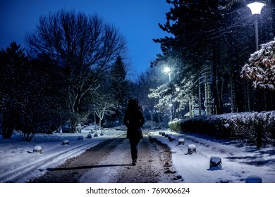 Woman walking in the park on the evening while snow is falling