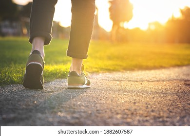 Woman walking in the park, outdoors. Closeup on shoe with rolled up jeans. Taking a step. New life concept