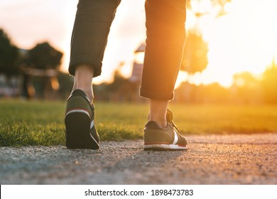 Woman walking in the park at sunset. Closeup on shoe with rolled up jeans. Taking a step. Woman on his way to a new better life. The way forward. New start, new life and freedom concept.