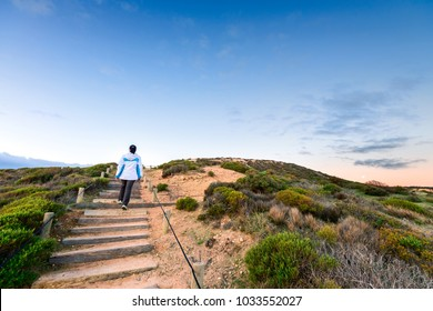 Woman walking up the pathway with wooden stairs at Hallett Cove Boardwalk at dusk, South Australia