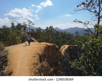 Woman walking peacefully with her little white dog in spectacular landscape with narrow trail and impressive cliff