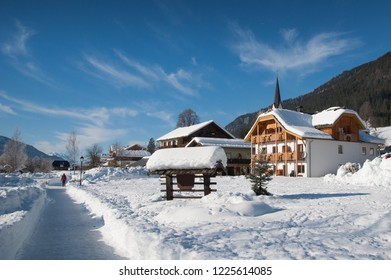 Woman walking in rural winter landscape, Weissensee, Carinthia, Austria