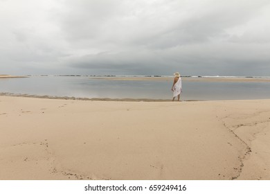 Woman walking in the sand of Barra do Rio beach - Rainy morning with dry moments.