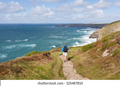 Woman walking the South West Coast Path near Mawgan Porth in Cornwall, UK.