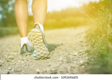 Woman walking in sport or hiking shoes. Jogging, trekking or training outside in summer nature, inspiring, motivational health and fitness concept.