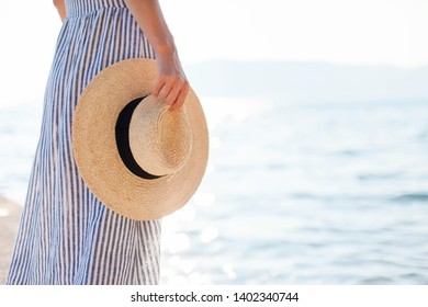 Woman is walking at summer beach. Girl is looking at sea waves. Female tourist in dress with straw hat is traveling and enjoying romantic vacation in ocean resort. Close up.
