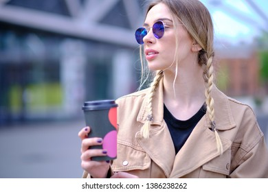 woman walking in the summer city street and drinking take away coffee in paper cup. Breakfast on the go.