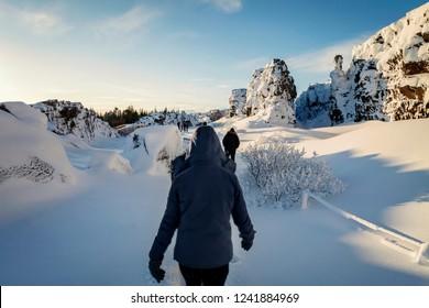 Woman walking through continental divide at Thingvellir national park; iceland.