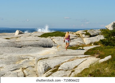 Woman walking through rocks and shrubs to beach (Cranberry Cove Nova Scotia Canada)